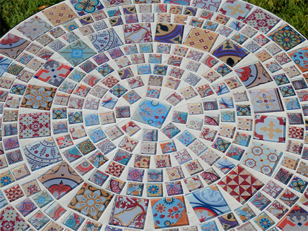 Close up image looking down onto the glass mosaic pattern on the top of the mosaic garden table for two