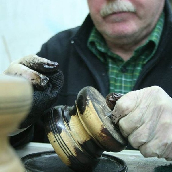 Hand crafted furniture - Applying the finish to the feet on a piece of Tetrad furniture