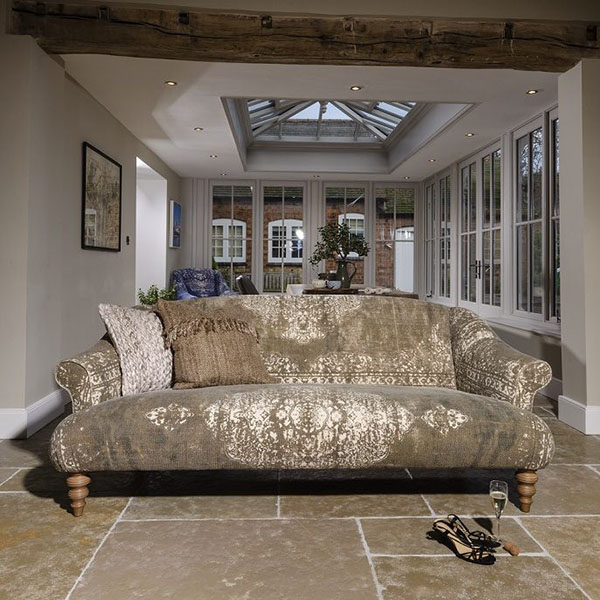 Tetrad Jacaranda Midi Sofa with a Jacaranda Chair in the background of the image